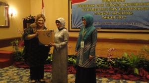 Dewi Hughes sebagai duta PAUD menyerahkan kenang-kenangan berupa laptop dari Intel kepada Ibu Zahra